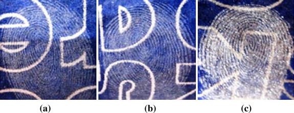 Résultats comparatifs de visualisation d'empreintes latentes sur du papier carbone avec  a) silica gel b) poudre blanche c) poudre grise claire